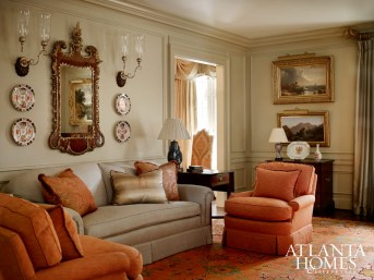 Bold decorative 19th-century elements, including the George III looking glass and pair of oil landscape paintings, are balanced by the contemporary touch of a sofa pillow made from a silk screen by the owners' son.