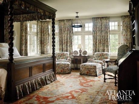 A canopied, barley-twist bed rests opposite a carved English secretary in the master bedroom. Floral fabric and a tole chandelier serve as powerful visual counterpoints to the highly decorative, early 20th-century Turkish carpet.