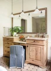 A vanity chair in a custom Pindler & Pindler fabric steals the show in the tailored master bathroom with pendant lights from Schoolhouse Electric.