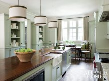 Benjamin Moore's Grecian Green unifies the spacious kitchen, a collaboration between Jane Hollman of Studio Entourage and architect Linda MacArthur. The pair designed the space to open up to both the formal dining room and a family-friendly den. Williams added drum-style ceiling fixtures with green and brown trim to harmonize with the rich wood countertops before layering in neutral accents.