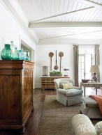 The family room embraces the airiness of the adjacent pool deck via expansive French doors. Staying true to that spirit, assemblages of transparent demijohn jars and primitive paddles serve as appropriate accents for a room that spills out to the pool.