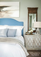 In the master bedroom, an antique table from Lydia's grandparents' estate flanks the bed. Painting by Gina Hurry for dk Gallery.