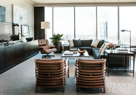 Furnishings with a certain nod to menswear-including a Ligne Roset sofa in gray flannel and an iconic Eames chair decked out in brown leather-give this condominium at The Ritz-Carlton Residences, Atlanta, Buckhead high-fashion status. The armchairs are by Roche Bobois. Meanwhile, see-through pieces like a whimsical glass chair by Spectrum appear barely there, but still function in a big way.