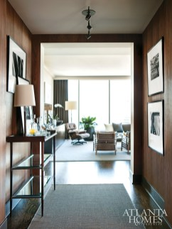 """In the walnut-clad entry, """"the client asked us to frame his black-and-white photography so he could switch out the photos,"""" says Brown. """"In a big glass high-rise, you don't have a lot of wall space, so this is a great way to rotate your art."""" The console table is by Baker."""