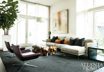 """""""You have to be careful not to over-design a modern home with too much furniture, otherwise the point of the space is lost,"""" advises architect and designer Joel Kelly, who helped create a thoroughly modern abode for a pair of Atlanta homeowners. Kelly warmed up the white living room with bursts of color, like the Bordeaux-colored B&B Italia chairs, and organic elements, like the standout natural tree root table. A contemporary arc lamp by Flos adds a visual punch to the room. The sofa, from Context Gallery, is accented by custom throw pillows in Zimmer + Rhode fabrics. The rug is by Stark Carpet."""