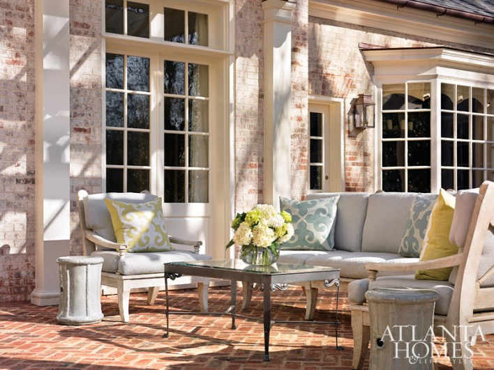 The back terrace is a sunny but secluded spot, thanks to an elegant arbor added by D. Stanley Dixon Architects. The sofa and chairs are by Niermann Weeks, available through Grizzel & Mann. Accent pillows are by Lacefield Designs, available through The Nicholson Gallery.