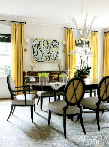 The dining room in a home designed by Margaux Interiors Ltd. is a study in contrasts. Sunny yellow curtains in a Schumacher fabric enliven the room's white walls, while an abstract painting by Amanda Talley is partnered with a mirrored Maison Jansen sideboard. Myran Allan's mouth-blown Murano glass chandelier strikes a dramatic yet delicate note above a sturdy table and leather-clad chairs.
