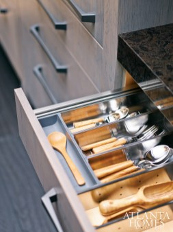 European storage solutions, specified by Bell, allowed interior cabinet space to be maximized to its fullest potential. Plate holders can actually be removed, enabling the cook to carry an entire stack at once. A more traditional-style faucet is the perfect juxtaposition to the contemporary cabinetry.
