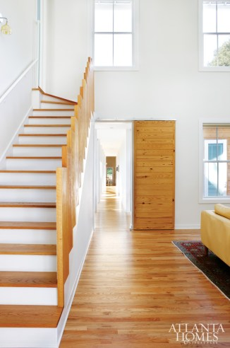 In the family room at the front of the home, a sliding door creates privacy when guests are visiting. The stairwell tread turns up vertically to become the railing, evocative of sculptural Southern staircases.