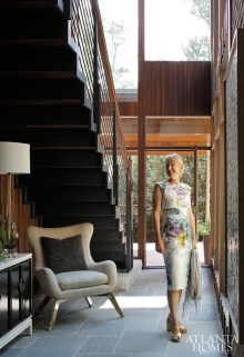 Homeowner and artist Leslie Wilson stands in the airy, two-story foyer, which is punctuated by a cantilevered staircase and walls paneled in solid black walnut. Antique console from Decades Antiques & Vintage. Chair and Murano glass lamp from 14th Street Antiques & Interiors.