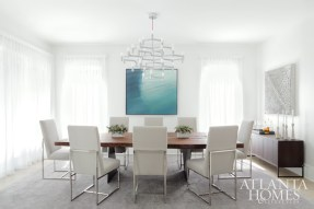 The dining room of this contemporary Decatur home is awash in bright light thanks to a thoughtful renovation by design team Rodolfo Castro, Julie Witzel and Lefko Design + Build. Custom walnut slab dining table by Taylor Donsker Design. Dining chairs by Mitchell Gold + Bob Williams. Credenza by Desiron. Painting over console from Bill Lowe Gallery.