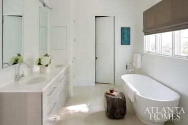 The master bathroom is state-of-the art-and fuss-free. Art from Bill Lowe Gallery. Stump stool by Chip and Company at Martin Nash.
