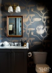A Cole & Son wallpaper delights with its metallic sheen in a powder room.
