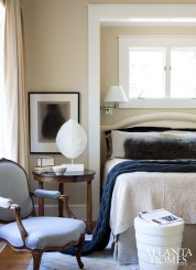 """""""It's all about balancing contrasting colors,"""" says Brown of the lake home's mix of dark and light tones. The bedroom's armchair, covered in a cozy Holland & Sherry wool flannel, was purchased in Paris, while the plaster tortoise shell and the ceramic drum table hail from Townhouse."""