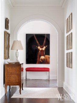 A graceful archway off the foyer frames a Joseph Guay photograph and custom bench by Smithworks Iron & Design.