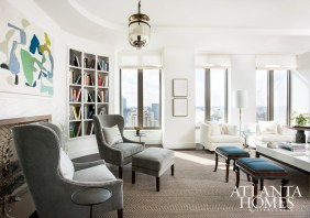 "On the 38th floor of the Residences at Mandarin Oriental, Atlanta, ""each piece of furniture is curated and not a placeholder,"" says Barbara Westbrook. In the living room, that thoughtful mix includes modern seating, such as grey wing chairs from Bungalow Classic, and a pair of antique stools in teal blue wool from Holland & Sherry."
