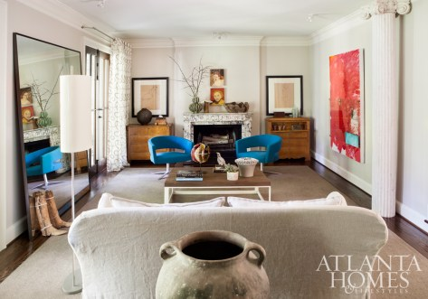Bright blue modern chairs and a bold painting by Jeff Jones electrify the living room, which overlooks the rear terrace and pool through two sets of French doors. A linen sofa anchors one end of the room, while paintings by Helen Durant preside over the mantel at the opposite end. A massive mirror reflects the room's eclectic mix.