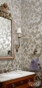 The powder room received a glamorous makeover with its Osborne & Little wallpaper in metallic silver and gold with a touch of the melon color pulled from the living room. An antique commode was retrofitted for the vanity, and the ornate mirror is from Parc Monceau.