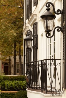 The façade features classic details that are hallmarks of Historical Concepts properties: perfect proportions, stately windows, handsome moldings, and an elegant gate leading to the beautiful front door door of a house that's sited within mature landscaping.