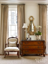 A bombe chest, bergere armchair, and gilt Rococo mirror create a quietly elegant vignette.