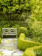 Landscape architect Joe Gayle created a series of distinct spaces, including this lined pathway that culminates with a bench overlooking climbing roses in bloom.