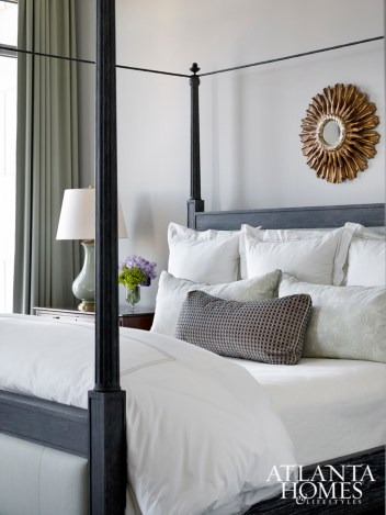 The master bedroom, dressed in soothing shades of gray, green and white, boasts clean lines thanks to a striking four-poster upholstered bed by David Iatesta and soft linens from Gramercy Fine Linens & Furnishings.