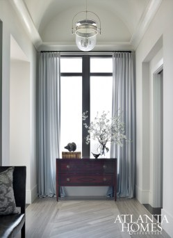 The gallery marble floor is inlaid on the diagonal to suggest a runner. A chest by Niermann Weeks, antique accessories and window treatments soften a tall window.