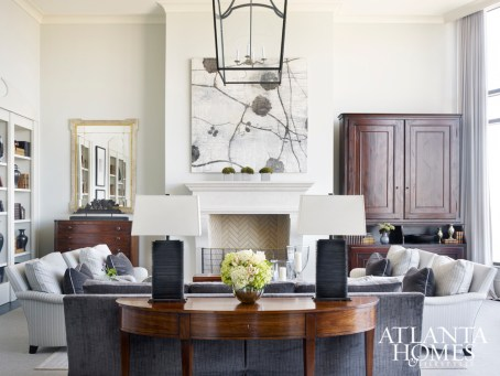 """""""I brought in some wood pieces to give this huge new space some feeling of history,"""" says interior designer Lauren DeLoach. """"I also like to use a smaller rug over a large one to anchor the furniture for a more intimate look."""""""