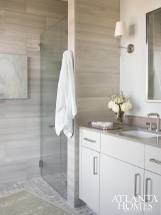 A sleek bathroom maintains the luxury hotel attitude of the Mandarin Oriental. Rug by Moattar, sconces from Circa Lighting and mirror from Restoration Hardware.