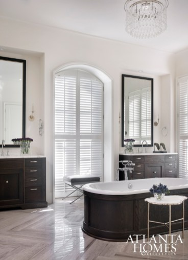 Block & Chisel cabinetry and a Waterworks tub rest on herringbone floors in the master bathroom.