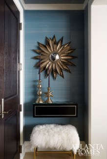 The entryway is wrapped in a silk Phillip Jeffries wallcovering for a rich look. A goat hair bench from Paul +, plaster candleholders from Townhouse and a metal starburst mirror up the foyer's glam quotient.