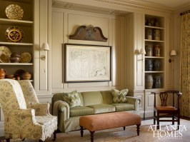The homeowners' sofa and ottoman were reupholstered to incorporate the soft color palette of the Oushak rug from Designer Carpets. A collection of Southern pottery and stoneware commands attention in the shelves flanking the seating area.