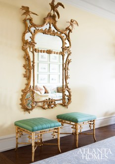 Gilt bamboo stools from John Rosselli balance a commanding antique Chippendale mirror.