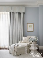 Pale blue adds a soothing touch in the guest bedroom, where a geometric side table from Huff Harrington injects a modern touch to the traditional room. Chair fabric by Kravet.