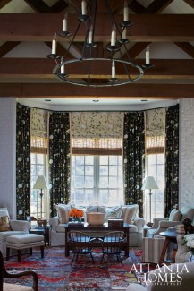 "The bay window is dressed in both black and cream versions of Cowtan & Tout's ""Snow Tree"" fabric. ""Nothing is prettier, when you look out the window and see flowers blooming, than to see flowers inside, too,"" says Topol."