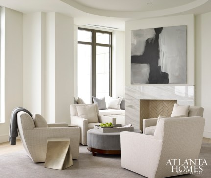 Interior designer Robert Brown set the living room's relaxing tone by painting walls and ceiling in Benjamin Moore's soothing White Dove. A set of four Baker, Knapp and Tubbs swivel chairs and an upholstered ottoman (covered in fabric by DeLany & Long) add sculptural presence around the fireplace, as does the small metallic drinks table by Baker.