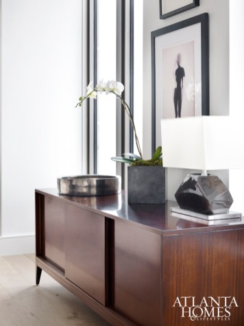 """Brown chose this streamlined Baker cabinet because, """"It doesn't speak too much."""" Hanging above are two black-and-white paintings, both from Townhouse by Robert Brown."""