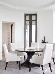 Brown divided the shapely living room into three distinct areas, including two for seating and a section for dining. Because the wife likes the legs of furniture to show, he chose skirtless dining chairs by Barbara Barry for Henredon.