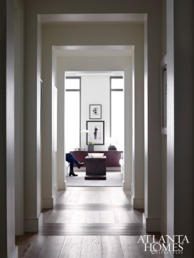 A long corridor leading to the living room serves as an art gallery with 12 niches, each displaying a work from the homeowners' extensive collection. To create a sense of intimacy, Brown broke up the pattern of the oak flooring by having it laid both vertically and horizontally.