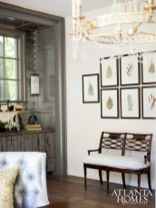 Framed botanicals and a charming settee provides a casually elegant transition area between the dining room, bar and stair hall.