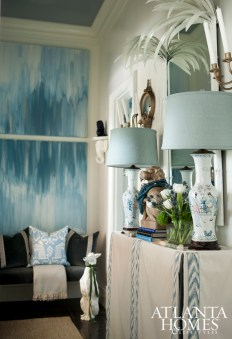 Vintage chinoiserie-style console lamps and a custom table skirt continue the color scheme, as do a set of abstract paintings.