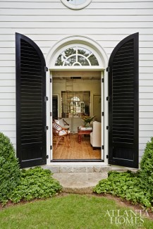 The French doors' curved shutters were painted a rich Charleston green for crisp contrast, and Dixon's intuitive architectural sight line provides a perfectly framed view to the living room beyond.