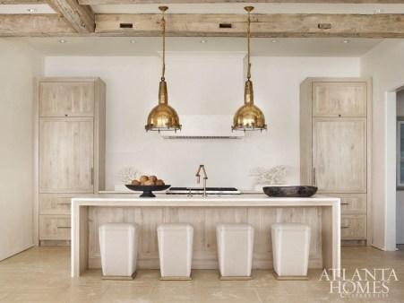 Antique light fixtures, a Venetian plaster hood and Lee Industries stools lend the sleek kitchen a calming effect.