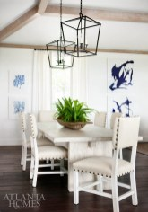 In the dining area, French linen chairs from Acquisitions sidle up to a reclaimed white elm table from Bungalow Classic.