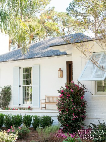 To liven up the home's exterior, the brick was painted white and accented with charming pale blue shutters.