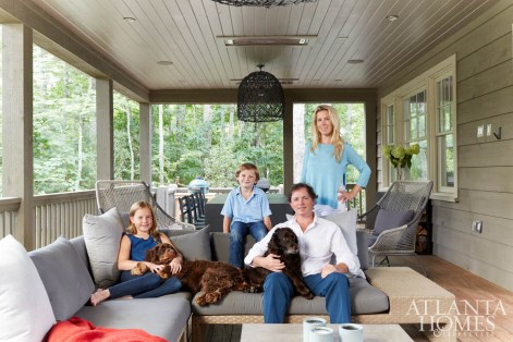 Homeowners Jennifer and Bonneau Ansley, shown on their back porch with daughter Blakely and son Beau, sought to create a modern yet cozy retreat. The outdoor sectional is from Kolo Collection.