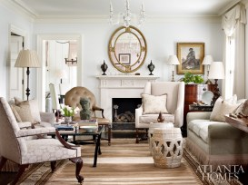 A palette of soft blue, green, creamy white, and brown flows from one room to another, including in the living room, where designer Jackye Lanham uses a mix of European antiques and comfortable upholstery to give the formal space an air of coziness.