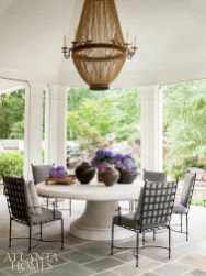 A supersized stone table by Michael Taylor accommodates a crowd on a covered gazebo overlooking the pool; a commanding chandelier adds drama.