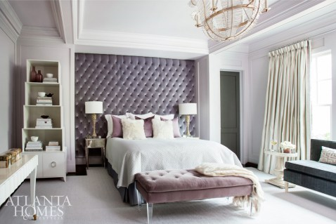 In the master bedroom, white lacquered and mirrored pieces up the glam quotient. A tailored Jan Showers settee in a charcoal gray provides a chic counterpoint. Morris took advantage of an existing bedroom niche and upholstered the entire space in a muted purple velvet by Theo.