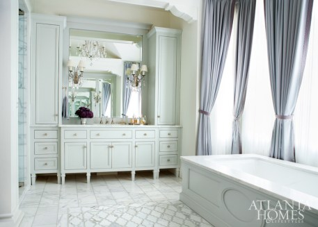 While the expansive master bath is wrapped in white, it is anything but staid, thanks to tile detailing on the floor and a touch of color in the window treatments.